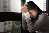 depressed women sitting near window and praying, alone, sadness, emotional concept