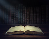 Open old book on a bookshelf background and the rays of light. Selective focus. Conceptual background on history, education, literature topics.