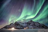 Aurora borealis with starry over snow mountain range with illumination house in Flakstad, Lofoten islands, Norway
