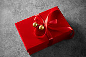 Christmas gift wrapped with red ribbon and decorated with christmas ornaments. Anniversary or Valentine's day gift.