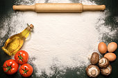 Spilled flour, rolling pin, eggs, bottle with butter. Ideas as a background