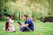 Relaxed young couple reading books while lying on grass
