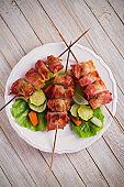 Chicken liver wrapped with bacon on skewers. Grilled liver kebabs