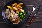 Beef steak diane with mushroom and leek cream sauce, potato fries and green peas in black plate on wooden background