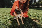 Young smiling woman is sitting on grass with her dog