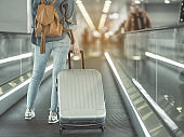 Woman holding luggage on moving stairs