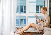 Laughing girl reading on window ledge