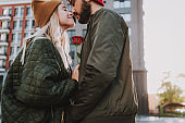 Beautiful young couple with flower touching noses on the street