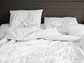 white bedding sheets and pillow on natural stone wall room background ,Unmade messy bed after comfort sleep concept
