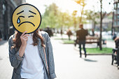 Woman is holding crying face sign outdoors