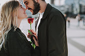 Beautiful young couple holding flower and touching noses on the street