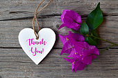 Thank You or thanks greeting card with bougainvillea flowers and decorative white heart on wooden background.