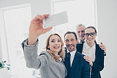 Portrait of attractive, cheerful, stylish, confident business persons standing in work place, station, shooting selfie on front camera, using smart phone, having break, pause, time out, rest, relax