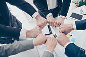 Close up top view cropped photo of experts in elegant classic outfit putting their fists together in a circle standing in work place, station, making ritual, sign, symbol of team, unity, support