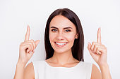 Close up portrait of young cheerful pretty girl gesturing up with her fingers. She is smiling, standing on the white background
