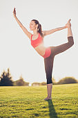 Chilling on the sun and fresh air. Wellbeing, wellness, vitality, freedom lifestyle. Young sporty woman is practicing yoga in the park outdoors in fashionable sport outfit