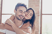 Beautiful couple of young brunette lovers are hugging indoors at home with love and tenderness, with closed eyes, dreaming of happy future together