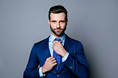 Portrait of serious fashionable handsome man posing in blue suit adjusting tie