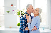 Portrait of sweet lovely attractive cheerful stylish couple in casual outfit hugging, woman holding bouquet of tulips, man kissing her lover in cheek, celebrating anniversary, having rest relax