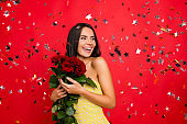 I'm the happiest woman in the world! Portrait of cheerful delightful attractive elegant tender gentle cute lovely luxurious woman with naked shoulders holding enjoying roses isolated on red background