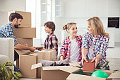 Young happy smiling family four persons unwrapping carton cardboard boxes with stuff in light kitchen living room, moving to new flat