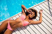 Cropped high angle view close up top above overhead view photo of sexual figure shape sporty multi-ethnical afro posing lady wearing stylish trendy bikini lying on white wooden floor by the blue pool