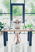Successful relaxed lawyer is resting at her work station and dreams of holiday which is coming, with big smile, in formal wear, hands are behind head, chill and serene mode, nice light interior