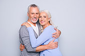 Portrait of delightful tender gentle elderly spouses who are relaxing, hugging, they have perfect ideal beaming shiny smiles, isolated on grey background