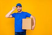 Portrait of handsome attractive cheerful bearded deliver with stubble in blue uniform holding card-board box, isolated over bright vivid yellow background
