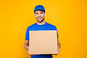 Portrait of handsome attractive cheerful bearded deliver with stubble in blue uniform giving you big cardboard box, isolated over bright vivid yellow background