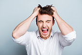 Emotions, stress, madness and people concept - crazy shouting man rending his hair in white shirt, screaming with close eyes and wide open mouth, holding hands on head over gray background