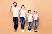 Full length portrait of beautiful adorable family, bearded father, blonde mother and their little children wearing jeans and white T-shirts, standing straight and gesturing up with fingers