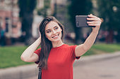 Straight-haired young beautiful smiling girl wearing casual red t-shirt outside in park, making selfie with smartphone