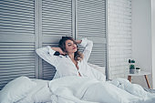 Rest, sleeping, comfort and people concept - young woman stretching in bed in light room at home bedroom, hands behind the head, dreaming about breakfast in bed