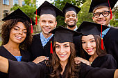 Selfie for memories. Six with cheerful graduates are posing for selfie shot, attractive brunette lady is taking, wearing gowns and mortar boards, outside on a summer day