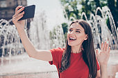 Young and charming brunette girl sends greetings to friends shooting a selfie video for her blog