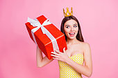 Portrait of pretty, nice, wondered, amazed, surprised woman having big red gift box in package with white bow, holding near ear, trying to know what inside, isolated on pink background