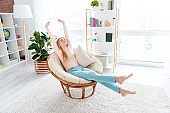Portrait of positive cheerful girl sitting on cane armchair in comfortable apartment flat making stretching with close eyes enjoying domestic atmosphere. Rent real estate concept