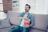 Happy laughing man in checkered shirt eating popcorn while watching comedies and having fun