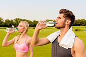 Fit healthy man and woman drinking water after exercise