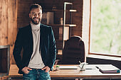Classic elegant stylish smart clever cheerful bearded business shark, ceo, leader in black jacket, holding hands in pockets at workplace, workstation