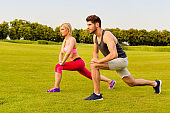 Sportive man and woman doing stretching exercises in the park