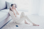 My mood depends on music! Charming relaxed careless beautiful woman is sitting on the floor, leaning on the sofa, listening to favorite tracks on her smartphone