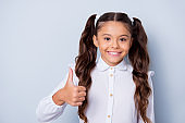 First grade schoolkid. Portrait of nice cute tender cheerful positive sweet latin stylish small little girl with curly pigtails in white formal shirt, showing thumb-up. Isolated over grey background