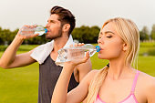 Portrait of tired man and woman drinking water after training