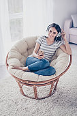 Cheerful young cute pretty woman enjoying music with headphones while sitting on comfort soft modern armchair at home