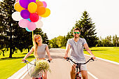 Happy cheerful man and woman riding bicycles with balloons