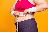 Concept of unhealthy eating and passive lifestyle. Cropped close up photo of fatty woman's body and hands measuring waist line, isolated on yellow background