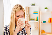 Portrait of young woman resting and drinking coffee in office