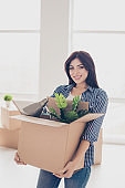 Charming smiling lady in checkered shirt and jeans  holding cardboard box with things in it